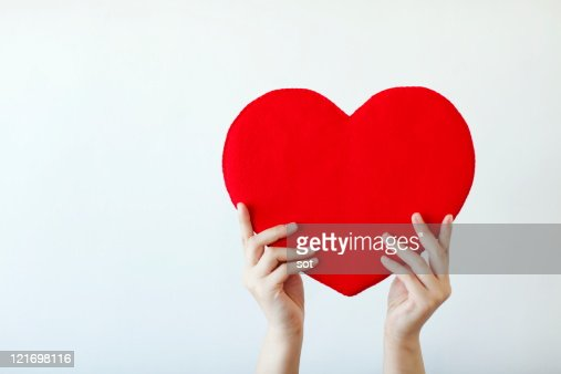 Hand of a woman lifting red heart,close up : Stock Photo