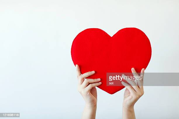 Hand of a woman lifting red heart,close up