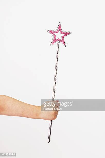 Hand of a young girl holding a pink and silver wand, close up