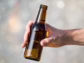 Hand of a young man with a beer bottle