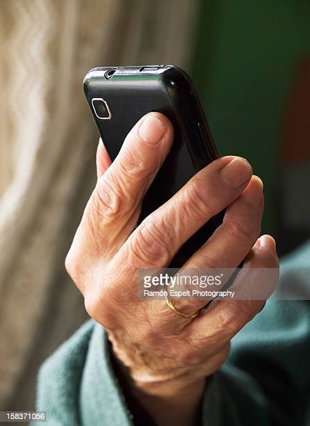 Hand of an elderly person holding a smartphone
