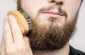 Hand of barber brushing beard. Barbershop customer,front view. Beard grooming tips for beginners. close-up