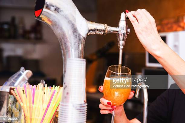 Hand of bartender pouring a large lager beer in tap