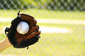Hand of Baseball Player with Glove and Ball over Field and Net