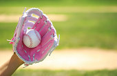 Hand of Baseball Player with Pink Glove and Ball over Field