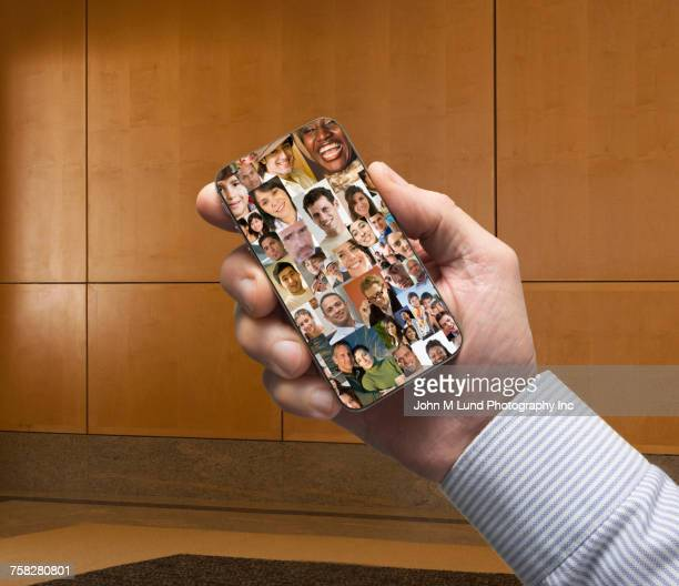 Hand of businessman holding social media cell phone in office