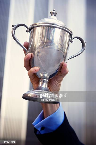 Hand of Businessman Holds Silver Trophy