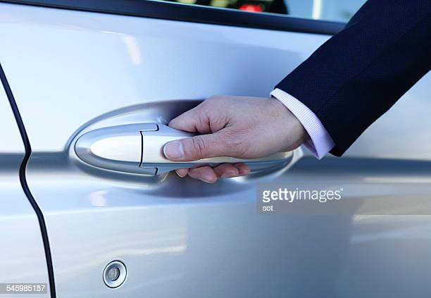 Hand of businessman opening door of car