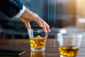 Hand of businessman touching glass of bourbon whiskey in building background