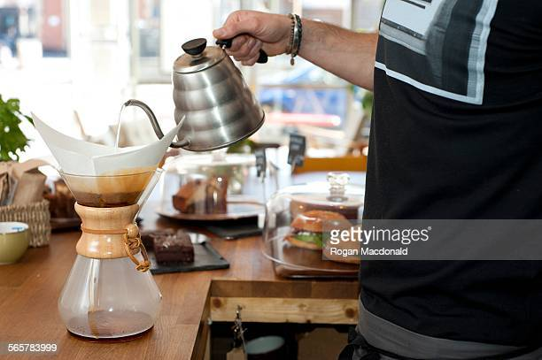Hand of cafe waiter pouring boiling water into filter coffee pot