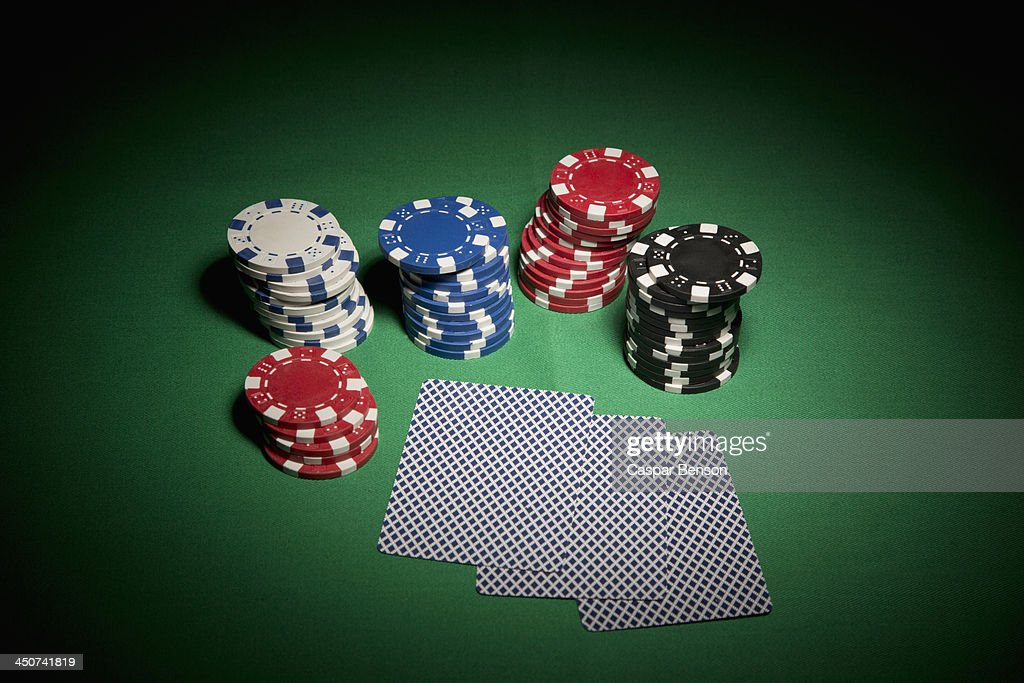 A hand of cards facedown, surrounded by stacks of gambling chips : Stock Photo