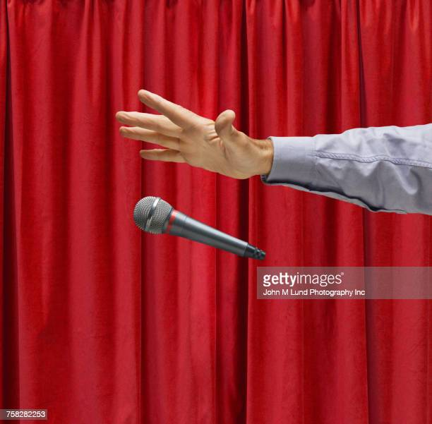 Hand of Caucasian man on stage dropping microphone
