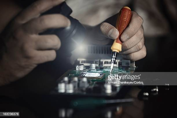 Hand of computer engineer doing repair of circuit board