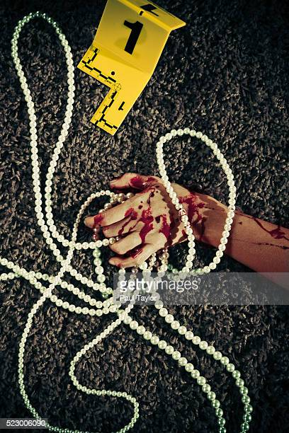 Hand of dead woman holding a pearl necklace