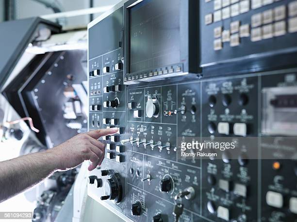 Hand of engineer operating CNC lathe control panel, close up