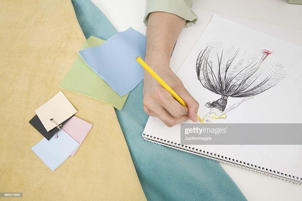 Hand of fashion designer drawing : Stock Photo