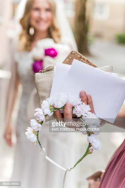 hand of female wedding witness with floral headband intercessions and clutch bag in foreground - bride out of focus in background