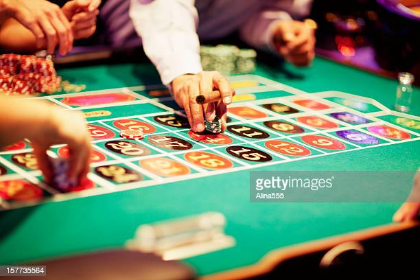 Hand of gambler making a bet at roulette table