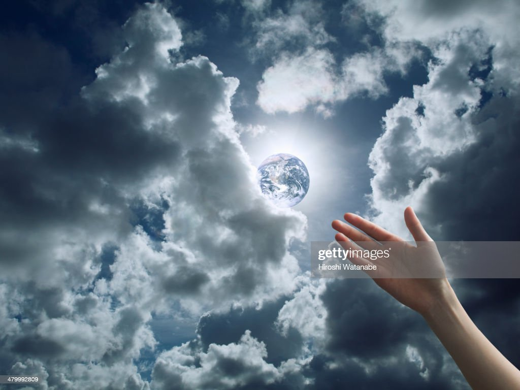 Hand of girl seems to reach to the Earth in the sk : Stock Photo