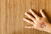 Hand of little girl with baby tattoo on bamboo background