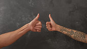 Hand of a man and a female hand with a tattoo on a dark background show the sign okay