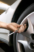 Hand of man checking tire air pressure with gauge