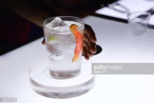 Hand of man holding a frosty glass with gin&tonic