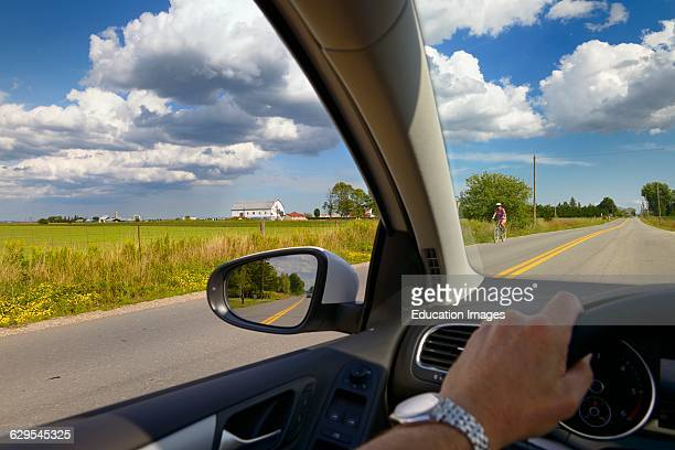 Hand of man on steering wheel of car driving down a country road with farm and clouds
