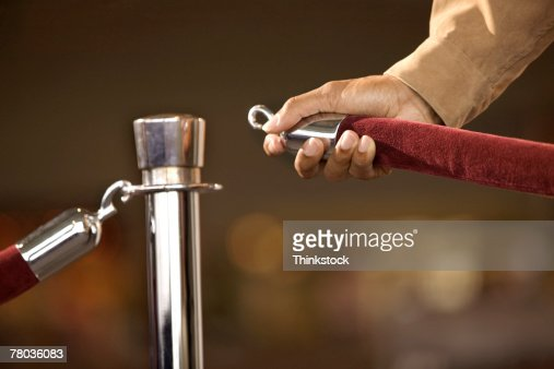 Hand of man opening rope barrier : Stock Photo