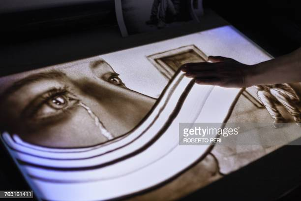 Hand of man wiping away sand drawing of woman crying, Cagliari, Sardinia, Italy, Europe