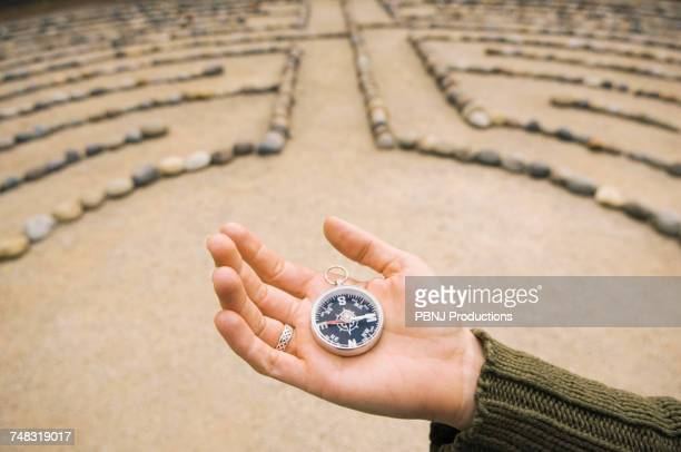 Hand of Mixed Race woman holding compass in maze