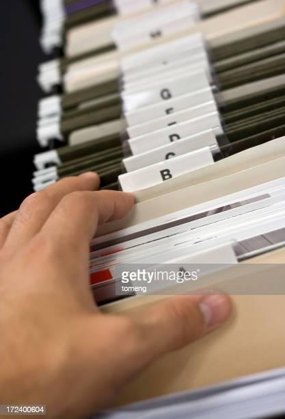 Hand der Person, die ein Dokument im Aktenschrank