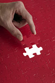 Hand of person putting last piece in jigsaw puzzle