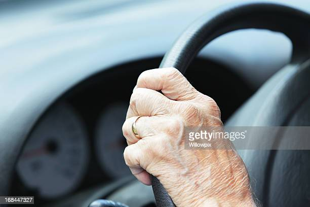 Hand of Senior Man Driver on Car Steering Wheel