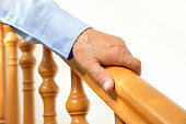 closeup of senior man using the wooden railing of stairs to go downstairs at his home