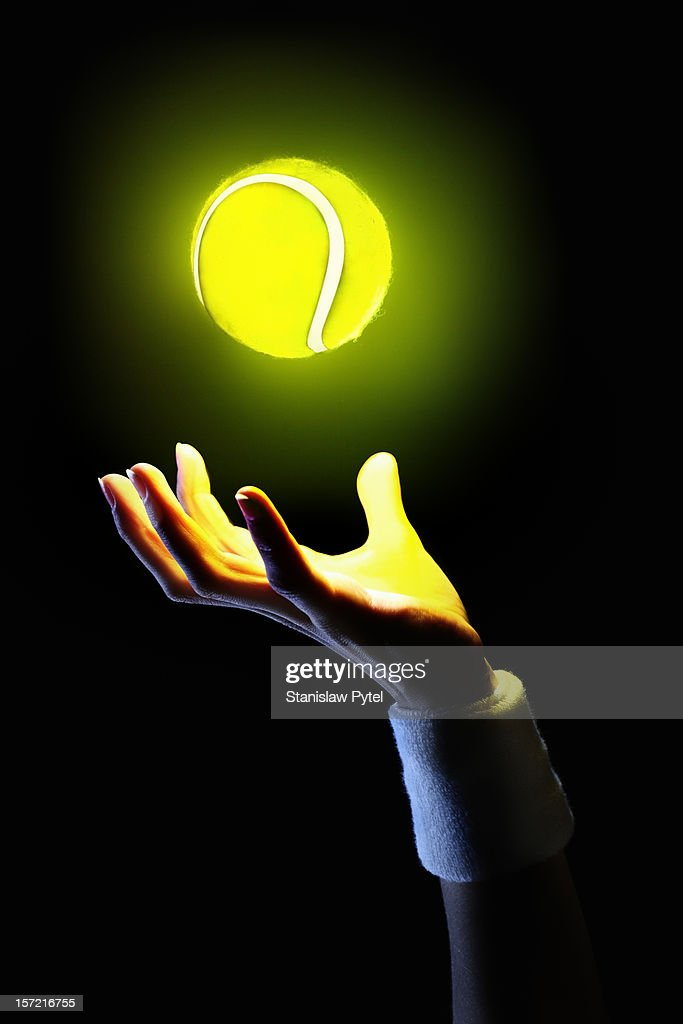 hand of tennis player holding glowing ball : Stock Photo
