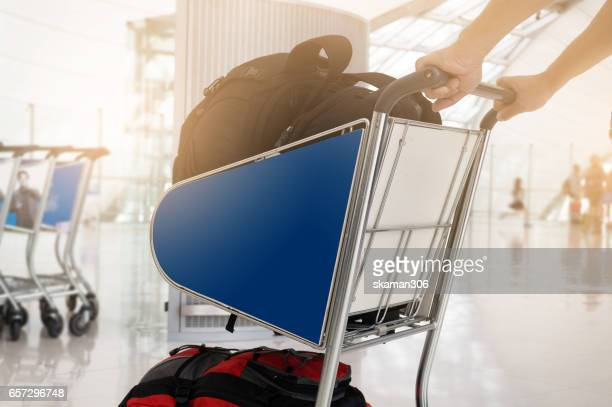 hand of traveller holding trolley in airport for connecting flight