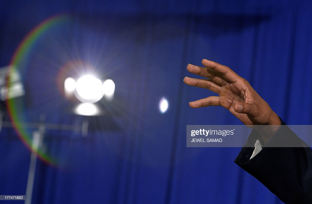 A hand of US President Barack Obama is seen as he gestures while answering a question during a town hall meeting at Binghamton University, on August 23, 2013 in Binghamton, New York. Obama is on a two-day bus tour through New York and Pennsylvania to discuss his plan to make college more affordable, tackle rising costs, and improve value for students and their families. AFP Photo/Jewel Samad