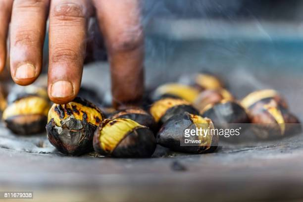 Hand Of Vendor Touching Hot Roasted Chestnuts