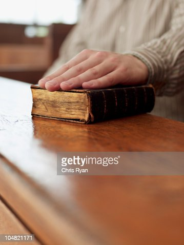 Hand of witness on Bible in courtroom : Stock Photo