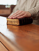 Hand of witness on Bible in courtroom