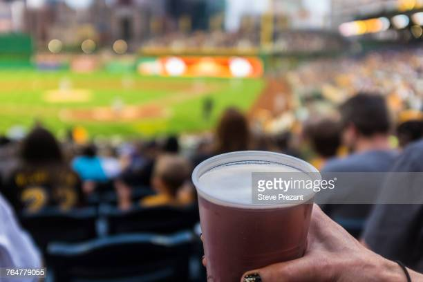 Hand of woman holding cup of beer in baseball stadium