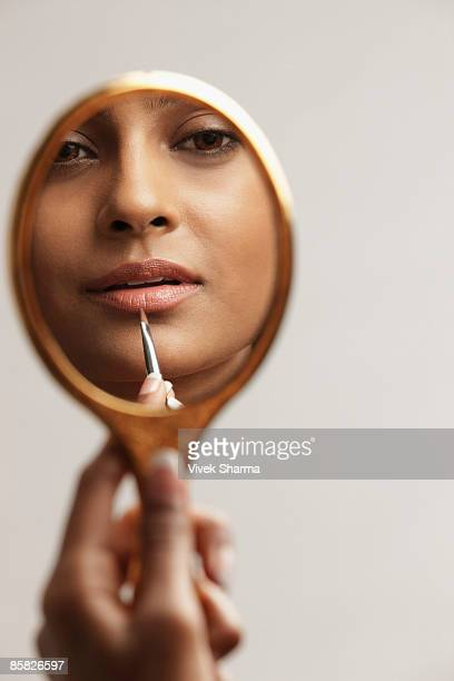 hand of woman holding up mirror with reflection