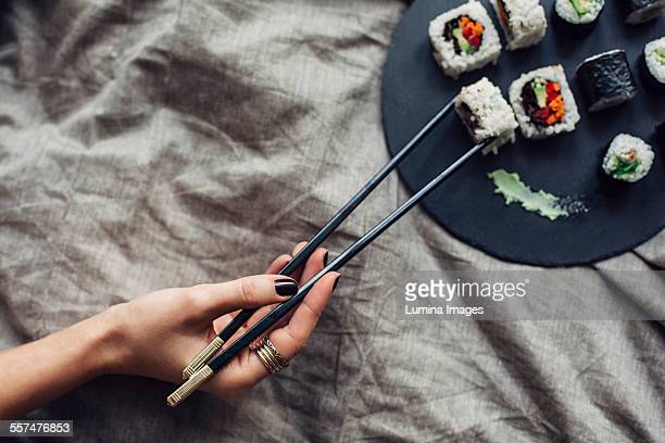 Hand of woman reaching for platter of sushi on bed