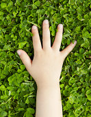 Hand of young girl on green grass