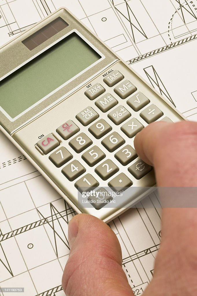 Hand on a calculator and blueprint : Stock Photo