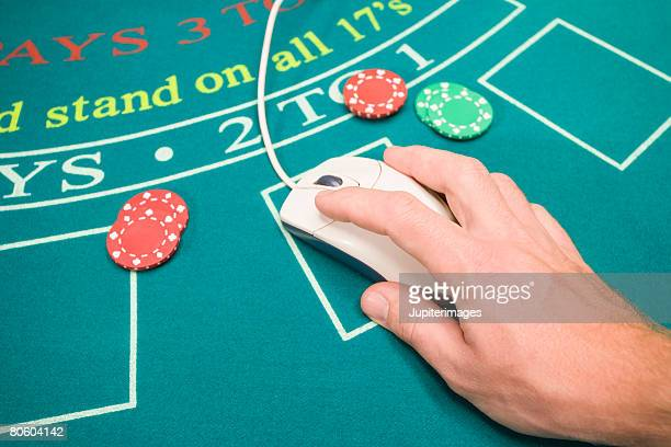 Hand on computer mouse on gambling table