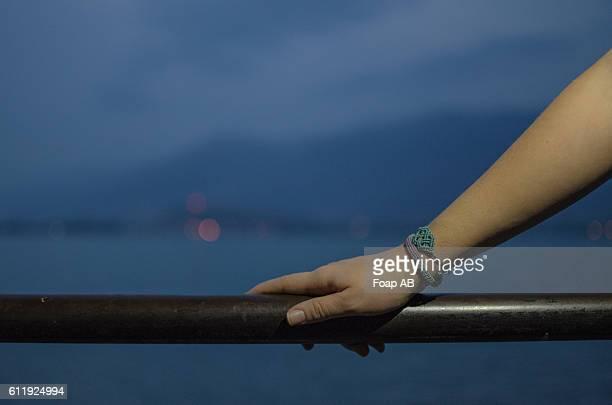 Hand on railing with bracelet