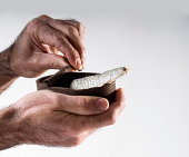 Hand opening a can of sardines in oil oxidized