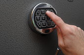 Hand enters combination on a digital lock of a safe's door